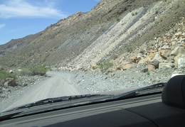 The road passes the edge of a pile of mine tailings