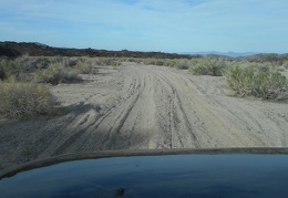 I pack up and leave my campsite by driving down the sandy road