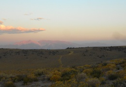 Pink sunset light illuminates the mountains in the distance
