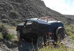 The FJ carefully squeezes past a few large rocks that could have been easily pushed aside