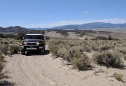 The FJ smiles as it reaches the crest of the sandy hill out of Adobe Valley